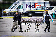 A body is removed from the scene after a shooting at a Fedex facility in Indianapolis, Friday, April 16, 2021.