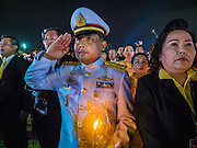 05 DECEMBER 2015 - BANGKOK, THAILAND: A Thai military officer salutes during the playing of the King's Anthem on the King's Birthday on Sanam Luang in Bangkok. Thais marked the 88th birthday of Bhumibol Adulyadej, the King of Thailand,  Saturday. The King was born on December 5, 1927, in Cambridge, Massachusetts. The family was in the United States because his father, Prince Mahidol, was studying Public Health at Harvard University. He has reigned since 1946 and is the world's currently the longest serving monarch in the world and the longest serving monarch in Thai history. Bhumibol, who is in poor health, is revered by the Thai people. His birthday is a national holiday and is also celebrated as Father's Day. He is currently hospitalized in Siriraj Hospital, recovering from a series of health setbacks.    PHOTO BY JACK KURTZ