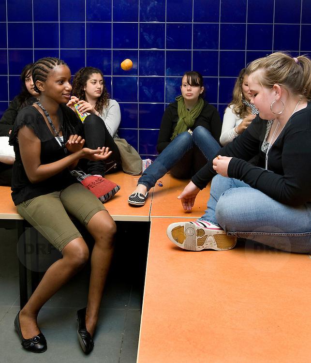 Nederland Rotterdam 5 juni 2008 20080604 Foto: David Rozing .Groepje VMBO leeringen van brede school Palmentuin in Ijsselmonde tijdens pauze  .De brede school is - in Nederland - een definitie voor de samenwerkende partijen die zich bezighouden met opgroeiende kinderen. Hierbij hoort in ieder geval onderwijs en welzijn, maar vaak ook kinderopvang, cultuur, sport, de bibliotheek, enz. In de praktijk is de brede school een plaats waar school en voor- en naschoolse opvang in elkaar samenvloeien..De brede school is een samenwerkingsverband tussen partijen die zich bezighouden met opgroeiende kinderen. Doel van het samenwerkingsverband is de ontwikkelingskansen van de kinderen te vergroten. Een ander doel kan zijn een doorlopende, en op elkaar aansluitende opvang te bieden. .De Brede School is geen nieuw begrip meer in Rotterdam. Sinds een aantal jaar breidt een groot aantal onderwijsinstellingen in het primair- en voortgezet onderwijs in Rotterdam het lesprogramma meer en meer uit met een keur aan activiteiten. Dit kunnen activiteiten zijn die zich richten op sociaal-emotionele, fysieke en cognitieve ontwikkeling van leerlingen, maar ook buiten- of voorschoolse activiteiten die de integratie en participatie van leerlingen en ouders bevorderen..Scholen werken samen met verschillende partners (organisaties, verenigingen, etc.) uit de buurt. Op deze manier sluiten binnen- en buitenschoolse activiteiten zo veel mogelijk op elkaar aan. Het doel? Om leerachterstanden te voorkomen en op te heffen, leer- en ontwikkelingsmogelijkheden te vergroten en de leerprestaties van leerlingen te verbeteren. En belangrijk: dat leerlingen kunnen ervaren waar ze aanleg voor hebben en hun talenten verder ontwikkelen. alle Brede Scholen in het Primair Onderwijs in Rotterdam per 1 januari 2007 verplicht voor-, tussen- en naschoolse opvang moeten aanbieden tussen 07.30 uur en 18.30 uur. Dit kan weer belangrijke gevolgen hebben voor het ontwikkelen van dagarrangementen. Daar wil Rot