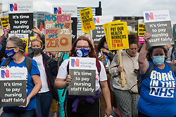 London, UK. 30th July, 2021. NHS staff march from St Thomas' Hospital to Downing Street to protest against the NHS Pay Review Body's recommendation of a 3% pay rise for NHS staff in England. The protest march was supported by Unite the union, which has called on incoming NHS England Chief Executive Amanda Pritchard to ensure that a NHS pay rise comes from new Treasury funds rather than existing NHS budgets and which is shortly expected to put a consultative ballot for industrial action to its members.