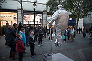 Silver painted living statue street performer sits totally still as if floating in mid air, and delighting passers by and tourists in Covent Garden, London, England, United Kingdom. There are many such performers making money in this way and having to increasingly be inventive in their guises.