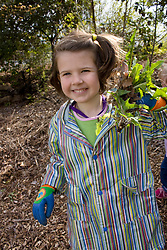 United States, Washington, Seattle, girl (age 5) with weeds at community service project in park