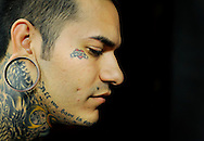 """Josh Butierres, 24, poses for a portrait on June 23 at Tribe Tattoo in Denver, Colo., where he and his brother, both tattoo artists, are employed. The brothers have a similar tattoo near one of their eyes that reads, """"mom"""" - a tribute to their mom who was shot in the face and killed by her boyfriend a little over two years ago during a domestic violence dispute."""