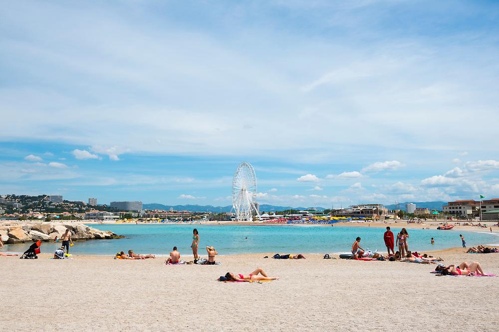 People enjoy a bank holiday at Plage Bonneveine, a beach near Marseille, France.