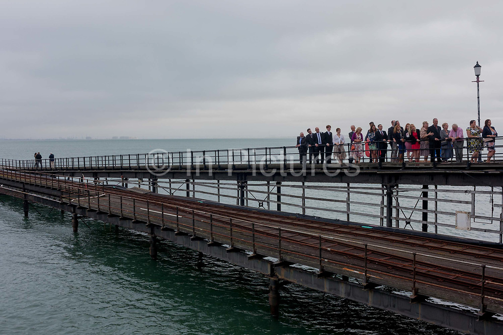 A wedding group stand on a grey day on Southend Pier, the worlds longest at a mile and a quarter, at Southend-on-Sea, Essex. Southend-on-Sea is a seaside town on the north side of the Thames estuary 40 miles 64 km east of central London. In its heyday, the working class visited from the capital when train transport allowed them to enjoy its beaches and the worlds longest pier. Its splendour faded on the advent of package holidays to Spain etc.