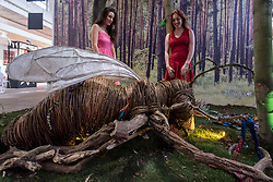 "© Licensed to London News Pictures. 04/10/2018. LONDON, UK. Staff members pose with a giant bee installation called ""The Stitcher"" by Louis Masai.  Preview of Moniker Art Fair, taking place during Frieze Week at the Old Truman Brewery, near Brick Lane.  Now in its tenth year, the fair embraces contemporary urban art from emerging and established artists  This year, the show's theme is 'Uncensored', shedding light on social, economic and ecological issues, and is open 4 to 7 October.  Photo credit: Stephen Chung/LNP"