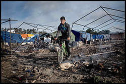 October 27, 2016 - Calais, Northern France, France - Image ¬©Licensed to i-Images Picture Agency. 27/10/2016. Calais, France. Calais Jungle Migrant Camp. Refugees past burning tents as they walk among the remains of  the migrant camp as Refugees leave the Calais Jungle migrant camp the day after it caught fire and the French police closed it down. Picture by Andrew Parsons / i-Images (Credit Image: © Andrew Parsons/i-Images via ZUMA Wire)