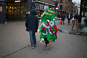 Man dressed up as a Christmas tree complete with tinsel and baubles, London, UK. Over the Xmas festive period you see a lot of people in fancy dress, but some people take this to a new level.