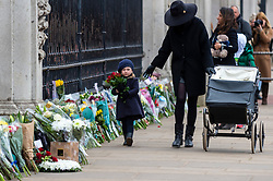 © Licensed to London News Pictures. 10/04/2021. LONDON, UK. A young well wisher arrive with flowers outside Buckingham Palace after the death of Prince Philip, aged 99, was announced the previous day.  Photo credit: Stephen Chung/LNP