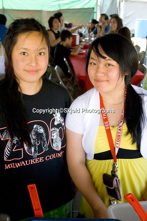 Happy Hmong SE Asian teenage women food servers. Hmong Sports Festival McMurray Field St Paul Minnesota USA