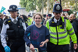 London, UK. 8 October, 2019. A climate activist from Extinction Rebellion is arrested in Millbank on the second day of International Rebellion protests to demand a government declaration of a climate and ecological emergency, a commitment to halting biodiversity loss and net zero carbon emissions by 2025 and for the government to create and be led by the decisions of a Citizens' Assembly on climate and ecological justice.