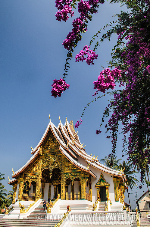 Flowers in front of Haw Pha Bang (or Palace Chapel) at the Royal Palace Museum in Luang Prabang, Laos. The chapel sits at the northeastern corner of the grounds. Construction started in 1963.
