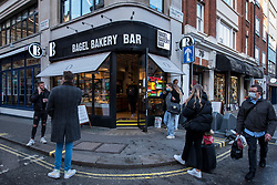 © Licensed to London News Pictures. 17/12/2020. LONDON, UK. People wait for orders outside a bagel bakery in Soho as the capital experiences Tier 3, Very High Alert Level, restrictions as the coronavirus pandemic continues. Under Tier 3, food make only be served as takeaway. Photo credit: Stephen Chung/LNP