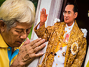 05 DECEMBER 2015 - BANGKOK, THAILAND:  A woman prays with a portrait of the King of Thailand in the plaza at Siriraj Hospital on the 88th birthday of Bhumibol Adulyadej, the King of Thailand. Hundreds of people crowded into the plaza hoping to catch a glimpse of the revered Monarch. The King has lived at Siriraj Hospital off and on for more than four years.    PHOTO BY JACK KURTZ
