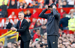 Manchester United caretaker manager Ole Gunnar Solskjaer (left) and Liverpool manager Jurgen Klopp react from the touchline during the Premier League match at Old Trafford, Manchester.