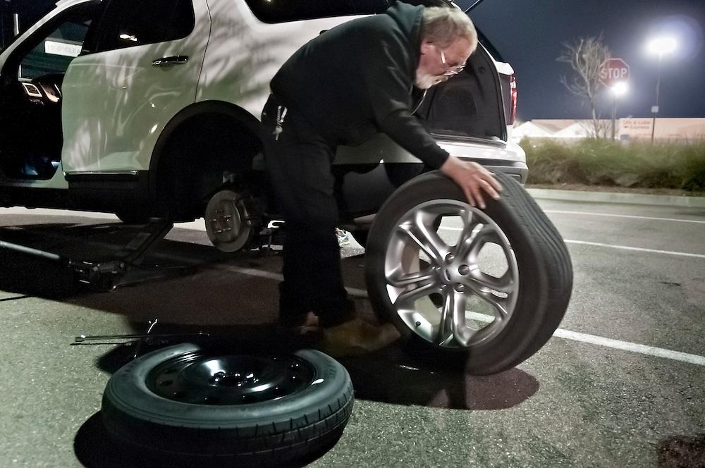 Ein Mann wechselt einen Autoreifen nach einer Panne |  man changes a flat tir. A spare tire, spare tyre
