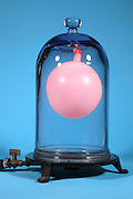 A balloon is placed in a vacuum chamber and the air is removed.  As the air is removed the pressure drops causing the air trapped in the balloon to expand.  The trapped air expands to many the original volume and the balloon grows in size.  This image is part of a series taken at different vacuum pressures.