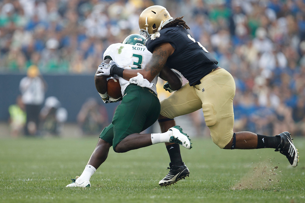 Notre Dame outside linebacker Ishaq Williams (#1) makes the tackle on South Florida running back Darrell Scott (#3) in action during NCAA football game between Notre Dame and South Florida.  The South Florida Bulls defeated the Notre Dame Fighting Irish 23-20 in game at Notre Dame Stadium in South Bend, Indiana.