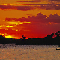 Lake of the Woods, Ontario, Canada. Sun sets over a small fishing boat.