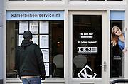 Nederland, Nijmegen, 8-2-2012Een jonge man staat voor de ruit van een kamerbemiddelingsbedrijf, kamerbeheerservice.nl.Foto: Flip Franssen/Hollandse Hoogte
