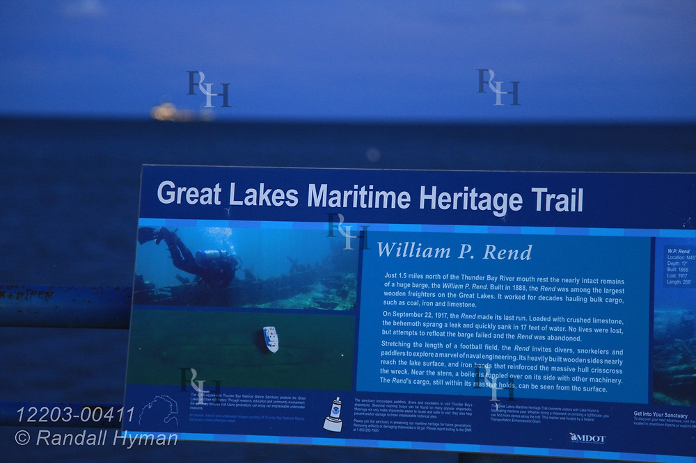 Great Lakes Maritime Heritage Trail sign along breakwater frames Lake Huron on a September evening in Alpena, Michigan.