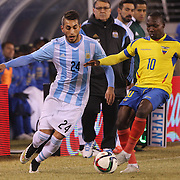 Walter Ayovi, (right), Ecuador, is challenged by Roberto Pereyra, Argentina, during the Argentina Vs Ecuador International friendly football match at MetLife Stadium, New Jersey. USA. 31st march 2015. Photo Tim Clayton