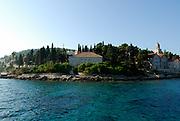 Coastline near old town of Korcula, with Dominican Church and Monastery of Saint Nicholas (Sveti Nikola), viewed from the sea. Island of Korcula, Croatia.
