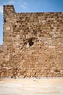Tripoli, Lebanon - September 7, 2010: The impact crater of a rocket scars the wall of the historic Citadel in Tripoli, Lebanon. The rocket's metal shell is still visible inside the crater. According to a guide, the rocket is from fighting in the 1980s.