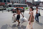 Transport worker carrying a heavy load on his shoulders using a yolk, contrasted against a young woman of relative wealth in comparison in Shanghai, China. Migrant workers such as this carry unbelievably heavy loads around the city for very low fees.