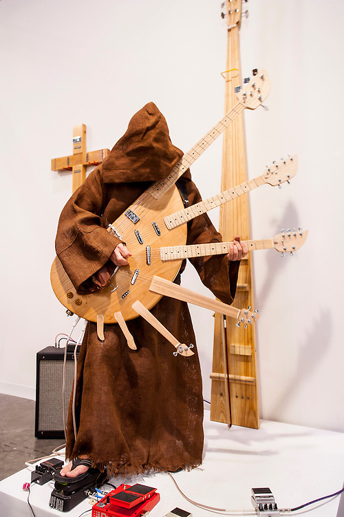 An artist wearing a hooded monk's robe plays a seven-necked, electric guitar at Art Basel Miami Beach 2007