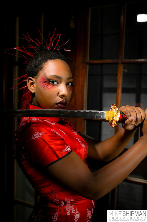 A portrait of an African-American woman wearing a red Oriental gown and a Japanese Katana sword