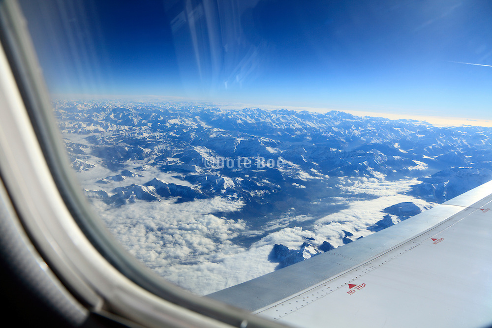 commercial passenger airplane flying over the Alpes