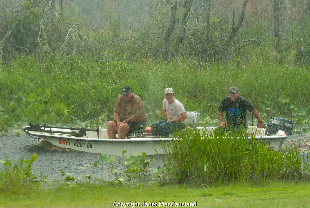 A rain and hail storm in the Okefenokee Swamp in Florida has put a damper on these three fishermen who are seen returning soon after departing the dock.