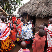 Wilson's wedding day...Wilson's wife is waiting outside her new home. Wilson is inside with his family and they will according to tradition officially invite her in to share the house...It is mainly Maasais who live in the Loita Hills up above the Serengeti plains. They live in small villages and communities called bomas and live mainly of raising and selling live stock such as cattle and goats. Its a very remote region in Kenya, hard to get to without a four wheel drive with very little infrastructure and up till 2010 no mobile phone network. The Maasais are well known though out Kenya and the world for their colorful clothing and their way of keeping their old traditions alive.