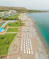 Aerial view of beach resort lined with white parasols on Rhodes island, Greece.