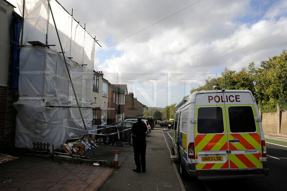 © Licensed to London News Pictures. 12/09/2011. Chatham,Kent,UK. Police tend to flowers at the scene of the fire today (12/09/11). A fourth arrest has taken place over a fatal house fire. Officers from Kent Police's Serious Crime Directorate arrested a 21-year-old woman in the Coventry area this afternoon.The arrest brings the total to four people. All are being questioned on suspicion of murder.Melissa Crook, 20, and her 15-month-old son Noah died in a house fire in Chatham Hill, Chatham, early on Saturday. Photo credit : Grant Falvey/LNP