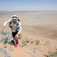 26 March 2007:  #344 Olivier Assant of France reaches summit of jebel El Otfal, 947 meters and an average 25% slope, during the second stage (21.7 miles) of the 22nd Marathon des Sables between Khermou and jebel El Otfal. The Marathon des Sables is a 6 days and 151 miles endurance race with food self sufficiency across the Sahara Desert in Morocco. Each participant must carry his, or her, own backpack containing food, sleeping gear and other material.