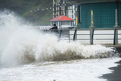 © Licensed to London News Pictures. 13/10/2018. Aberystwyth, UK. High tide at 11am and with winds gusting at 50mph and more, the tail end of Storm Callum still has enough energy to bring huge waves crashing into the seafront and promenade in Aberystwyth on the Cardigan Bay coast of west wales. Photo credit: Keith Morris/LNP