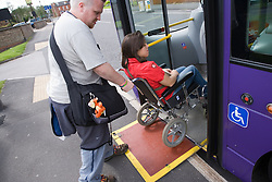 Young woman with cerebral palsy in a wheelchair with her boyfriend getting on a bus using a mobility ramp,