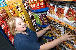 Young woman working in Blockbuster video rental shop; arranging shelves of crisps; Merseyside