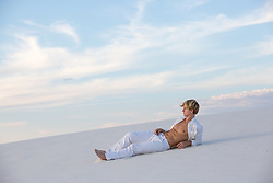 hot man with open shirt relaxing on a sand dune