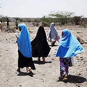 School girls head home after school through the desert in Somaliland. The chool is run by the charity African Educational Trust. The children walk up to 7 km to get to school through the rough terrain, often on their own.
