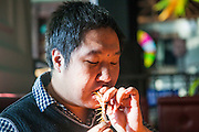 CHANGCHUN, CHINA - NOVEMBER 18: (CHINA OUT) <br /> <br /> Dancing Teacher Performs With Poisonous Creatures<br /> <br /> Tian Jiashi puts a live centipede into his mouth on November 18, 2015 in Changchun, Jilin Province of China. 33-year-old dancing teacher Tian Jiashi has been fascinated and fed scorpions, vipers, centipedes, lizards and spiders at home for seven years in Changchun. Tian sometimes performed swallowing these poisonous creatures onstage even being bit hundreds of times. <br /> ©Exclusivepix media