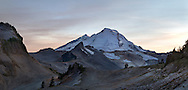 Sunset over Mount Baker, Coleman Pinnacle and Happy Bunny Butte (R to L) in early Fall.  The 2014/2015 winter had very little snow, so there is likely less snow/ice here than a typical October day. Photographed while hiking the Chain Lakes Trail (on side of Table Mountain) in the Mount Baker Wilderness, Washington State, USA.