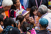 05 JANUARY 2014 - BANGKOK, THAILAND: SUTHEP THAUGSUBAND, leader of the anti-government movement, kisses a baby during a march through Bangkok Sunday. Suthep is a former Deputy Prime Minister and member of the opposition Democrat Party who resigned to organize the protests against the Pheu Thai government.  He led the protestors on a march through the Chinatown district of Bangkok. Tens of thousands of people waving Thai flags and blowing whistles gridlocked what was already one of the most congested parts of the city. The march was intended to be a warm up to their plan by protestors to completely shut down Bangkok starting Jan. 13.     PHOTO BY JACK KURTZ