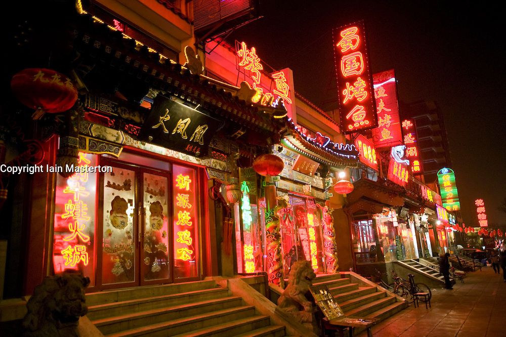 """Bright neon lights and red lanterns at night outside traditional restaurants on """"Ghost Street"""" in central Beijing, a historic street famed for its many restaurants February 2009"""