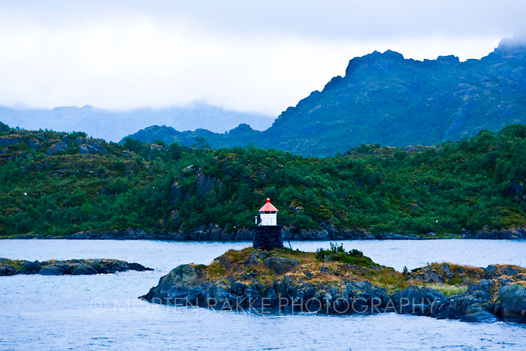 Norway, lighthouse on lake with mountains in background