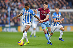 Huddersfield Town's Steve Mounie (left) and West Ham United's Declan Rice battle for the ballduring the Premier League match at the John Smith's Stadium, Huddersfield.