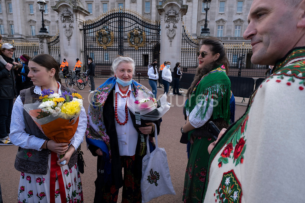 Polish family wearing traditional highlander dress arrive to lay floral tributes following the death of Prince Philip, Duke of Edingburgh outside Buckingham Palace on 11th April 2021 in London, United Kingdom. Members of the public have been laying flowers outside the gates of the royal residence following his passing at the age of 99 on 9th April 2021. Prince Philip, Duke of Edinburgh was a member of the British royal family as the husband of Elizabeth II. Philip was born into the Greek and Danish royal families.