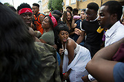 Groups of young men and women daggering behind a crowded sound system on Monday 28th August 2016 at the 50th Notting Hill Carnival in West London. A celebration of West Indian / Caribbean culture and Europes largest street party, festival and parade. Revellers come in their hundreds of thousands to have fun, dance, drink and let go in the brilliant atmosphere. It is led by members of the West Indian / Caribbean community, particularly the Trinidadian and Tobagonian British population, many of whom have lived in the area since the 1950s. The carnival has attracted up to 2 million people in the past and centres around a parade of floats, dancers and sound systems.